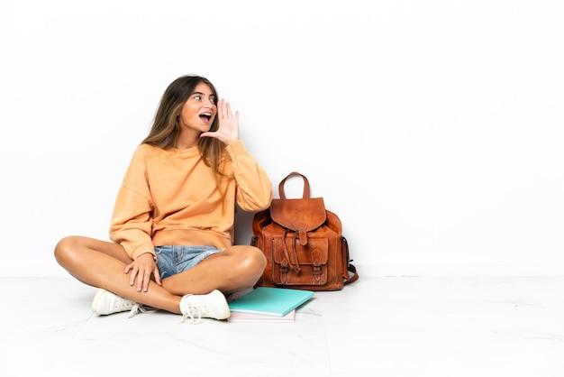 흰색 배경에 고립 된 노트북과 함께 바닥에 앉아 젊은 학생 여자가 입 벌리고 옆으로 외치고