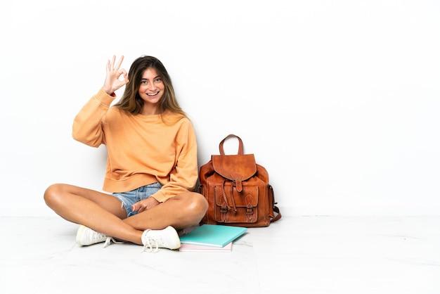 손가락으로 확인 표시를 보여주는 흰색 배경에 고립 된 노트북과 함께 바닥에 앉아 젊은 학생 여자