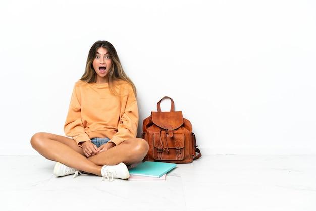 놀라운 표정으로 흰색 배경에 고립 된 노트북과 함께 바닥에 앉아 젊은 학생 여자