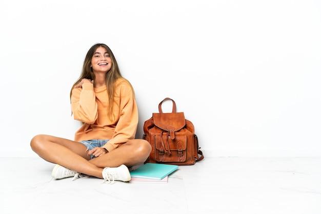 흰색 웃음에 고립 된 노트북과 함께 바닥에 앉아 젊은 학생 여자