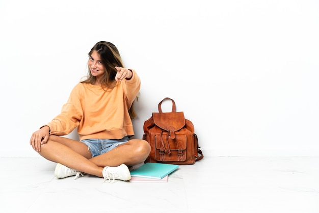 행복 한 표정으로 앞을 가리키는 흰색에 고립 된 노트북과 함께 바닥에 앉아 젊은 학생 여자