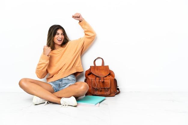 승리를 축하 흰 벽에 고립 된 노트북과 함께 바닥에 앉아 젊은 학생 여자