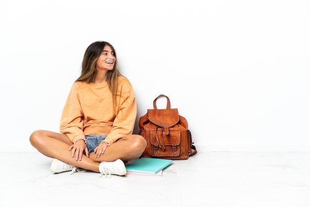 측면 위치에서 웃고 흰 벽에 고립 된 노트북과 함께 바닥에 앉아 젊은 학생 여자