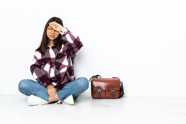 Молодой студент женщина сидит на полу с усталым и больным выражением