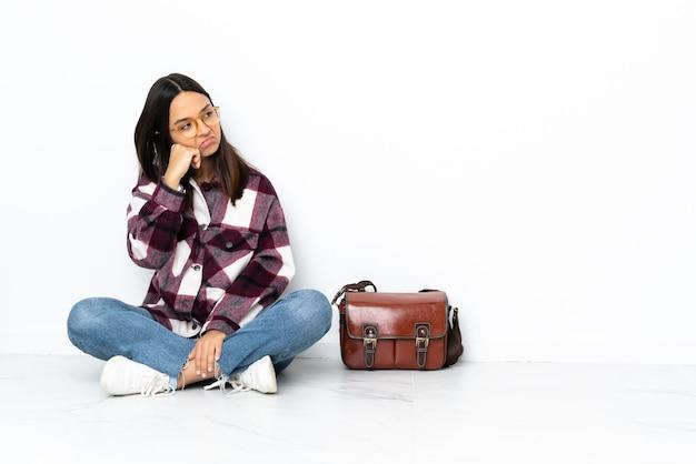 Молодая студентка женщина, сидящая на полу