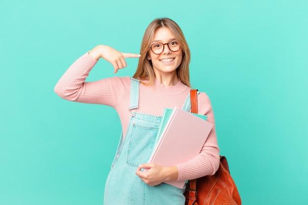 自信を持って笑顔の若い学生女性が自分の広い笑顔を指しています