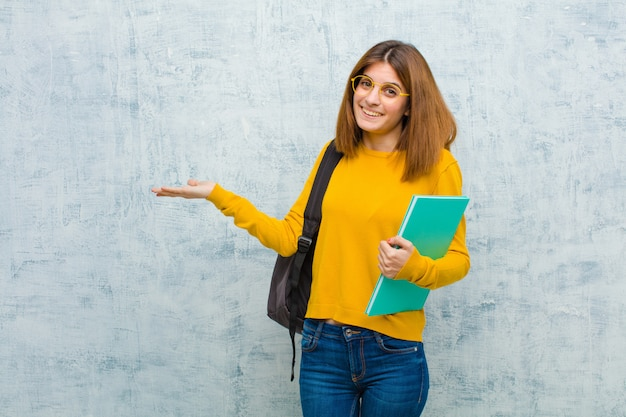 Young student woman smiling feeling happy carefree and satisfied pointing to concept or idea on copy space on the side