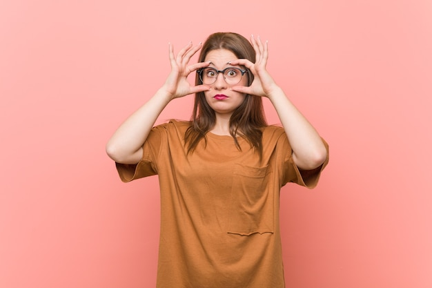 Молодая студентка женщина в очках держит глаза открытыми, чтобы найти возможность успеха.
