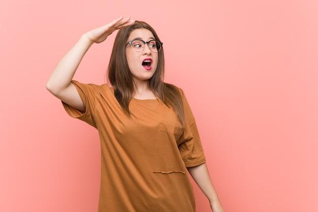 額に手を置いて遠くを見ている眼鏡をかけている若い学生女性。