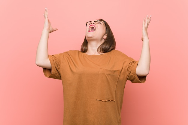 Young student woman wearing eyeglasses screaming to the sky, looking up, frustrated.