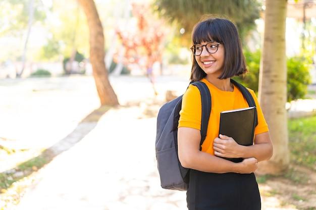 Молодая студентка выигрывает парк, держа ноутбук со счастливым выражением лица