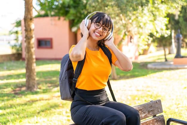 Молодая студентка выигрывает в парке, слушая музыку