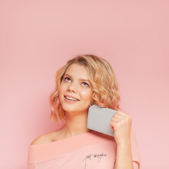Young student woman with colored hairs and tattoo holding passport on the pink background