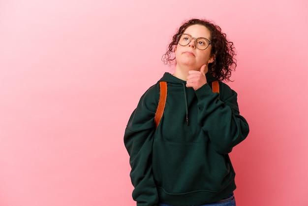 다운 증후군을 가진 젊은 학생 여자는 의심스럽고 회의적인 표정으로 옆으로 찾고 분홍색 배경에 고립.