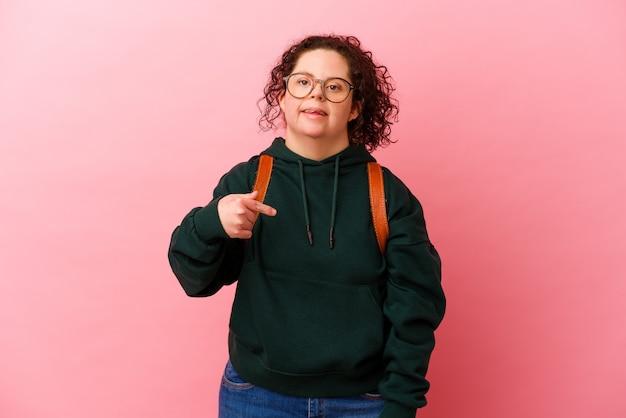 ピンクの背景の人がシャツのコピースペースを手で指しているダウン症の若い学生女性、誇りと自信を持って