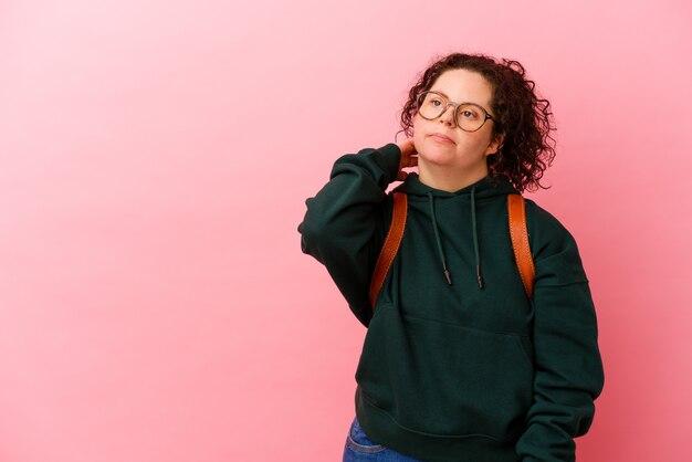 Молодая студентка с синдромом дауна изолирована на розовом трогательном затылке, думая и делая выбор.