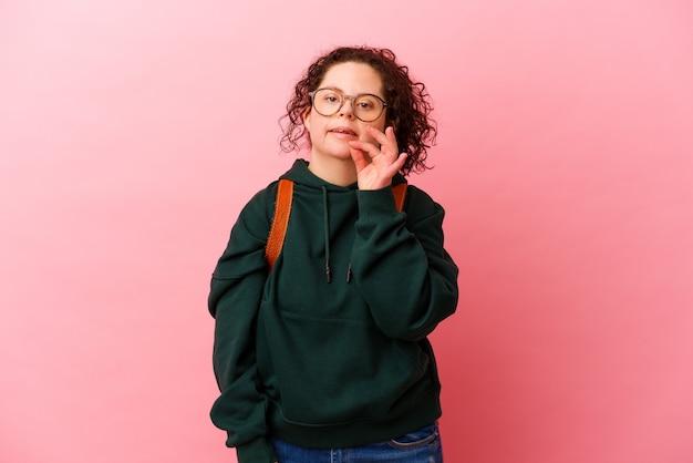 다운 증후군을 가진 젊은 학생 여자는 분홍색 벽에 손톱을 물고 긴장하고 매우 불안합니다.