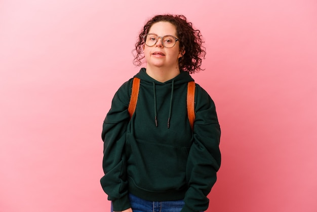 Молодая студентка с синдромом дауна, изолированная на розовой стене, смотрит в сторону улыбаясь, веселая и приятная