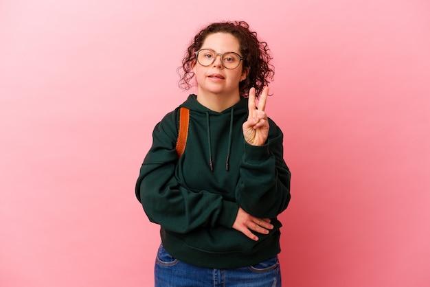 ピンクの壁に孤立したダウン症の若い学生女性は、指で2番目を示しています。