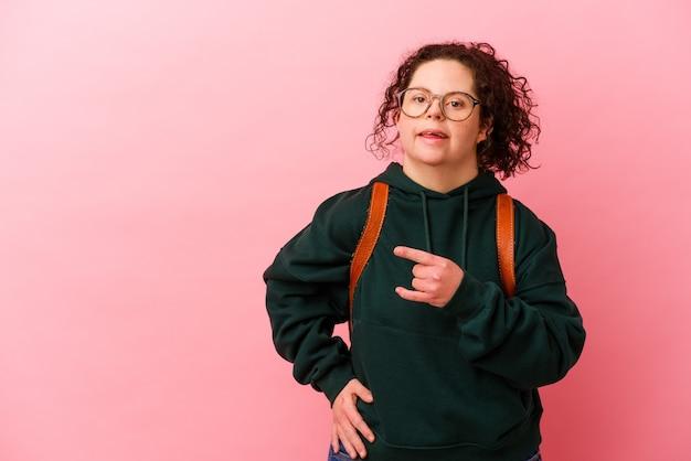 다운 증후군을 가진 젊은 학생 여자 웃 고 옆으로 가리키는 분홍색 벽에 고립 된 빈 공간에서 뭔가 보여주는.