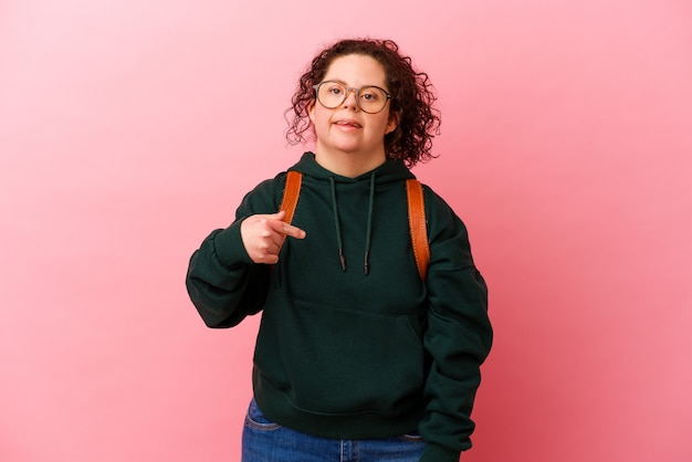 Young student woman with down syndrome isolated on pink background person pointing by hand to a shirt copy space, proud and confident