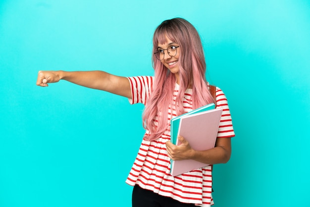 Young student woman with pink hair isolated on blue background giving a thumbs up gesture