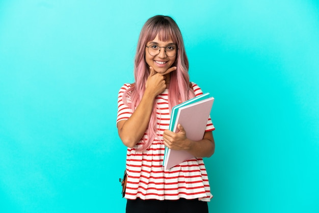 Young student woman with pink hair isolated on blue background happy and smiling