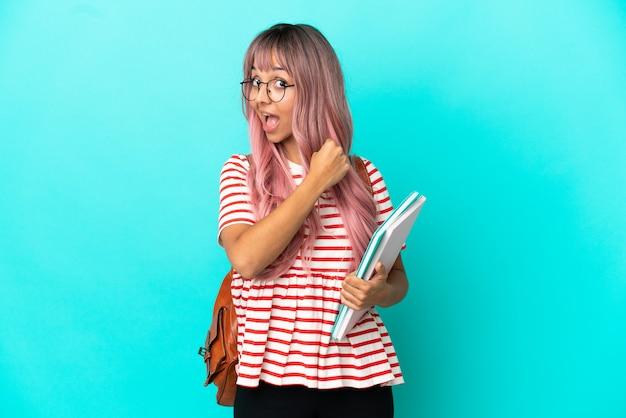 Молодая студентка с розовыми волосами на синем фоне празднует победу