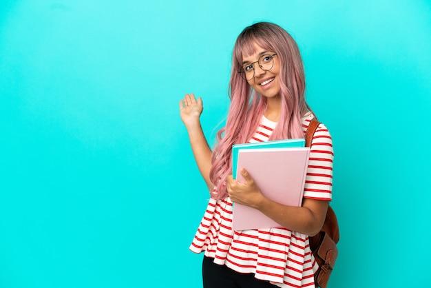 Молодая студентка с розовыми волосами изолирована на синем фоне, протягивая руки в сторону, чтобы пригласить приехать