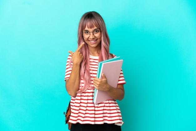 Молодая студентка с розовыми волосами, изолированными на синем фоне, показывает жест
