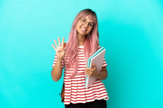 Молодая студентка с розовыми волосами, изолированными на синем фоне, счастлива и считает четыре пальцами