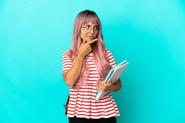 Молодая студентка с розовыми волосами, изолированными на синем фоне, сомневаясь