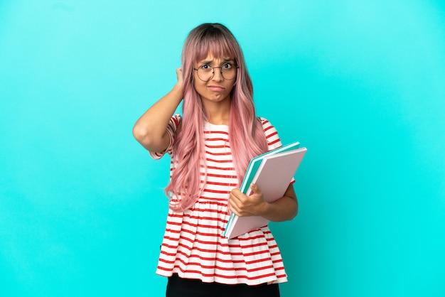 파란색 배경에 격리된 분홍색 머리를 가진 젊은 학생 여성