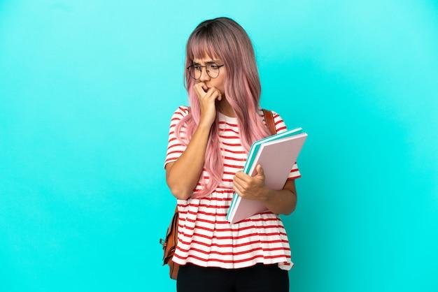 疑いを持っている青い背景に分離されたピンクの髪を持つ若い学生女性