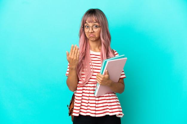 파란색 배경에 격리된 분홍색 머리를 가진 젊은 학생 여성이 손을 잡고 초대합니다. 당신이 와서 행복