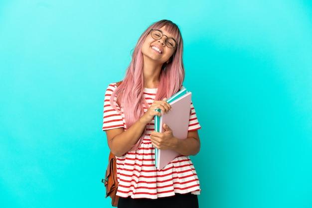 Молодая студентка с розовыми волосами, изолированными на синем фоне, смеясь
