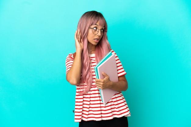 파란색 배경에 격리된 분홍색 머리를 한 젊은 학생 여성은 귀에 손을 대고 무언가를 듣고 있습니다.