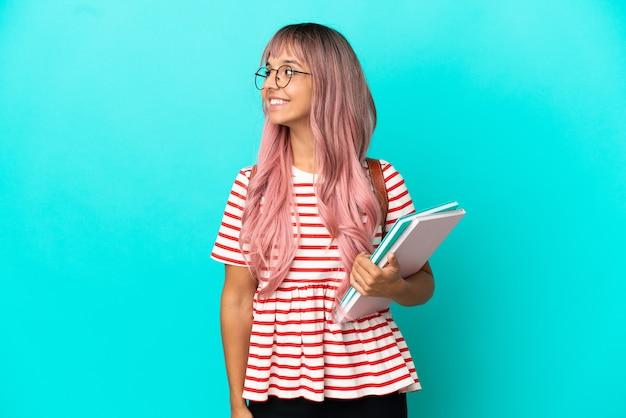 Молодая студентка с розовыми волосами, изолированными на синем фоне, глядя в сторону