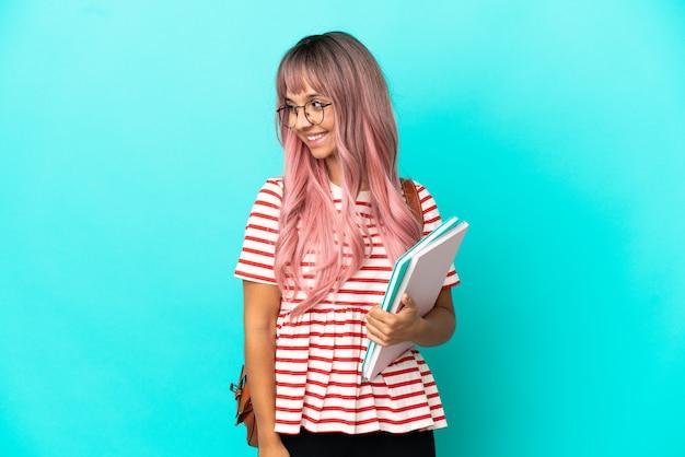 Молодая студентка с розовыми волосами, изолированными на синем фоне, смотрит в сторону и улыбается