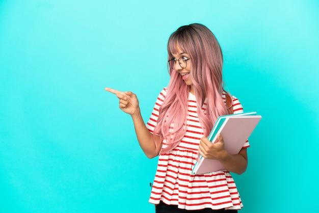파란색 배경에 고립 된 분홍색 머리를 가진 젊은 학생 여성은 손가락을 옆으로 가리키고 제품을 제시합니다.