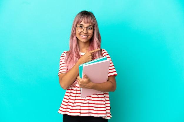 제품을 제시하기 위해 측면을 가리키는 파란색 배경에 격리된 분홍색 머리를 가진 젊은 학생 여성