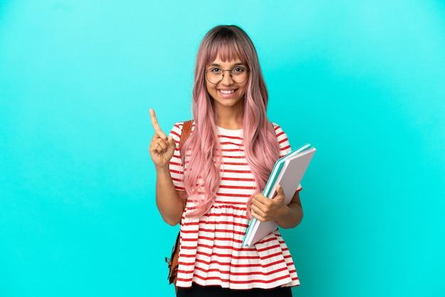 Молодая студентка с розовыми волосами изолирована на синем фоне, указывая на отличную идею