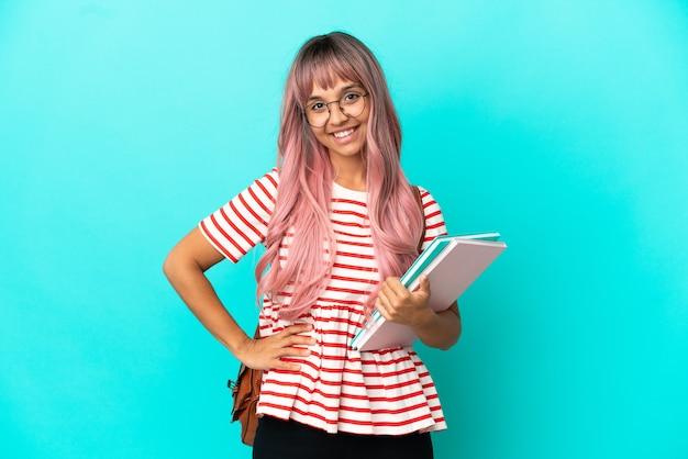 Молодая студентка с розовыми волосами, изолированными на синем фоне, позирует с руками на бедрах и улыбается