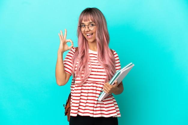 Молодая студентка с розовыми волосами, изолированными на синем фоне, показывает пальцами знак ок