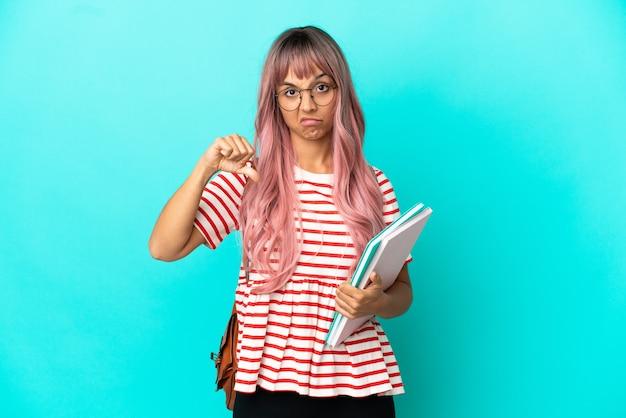 부정적인 표정으로 엄지손가락을 아래로 보여주는 파란색 배경에 고립 된 분홍색 머리를 가진 젊은 학생 여자