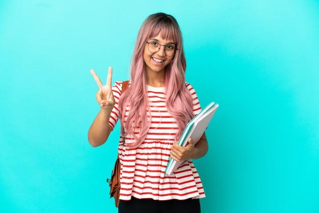 Молодая студентка с розовыми волосами, изолированными на синем фоне, улыбается и показывает знак победы