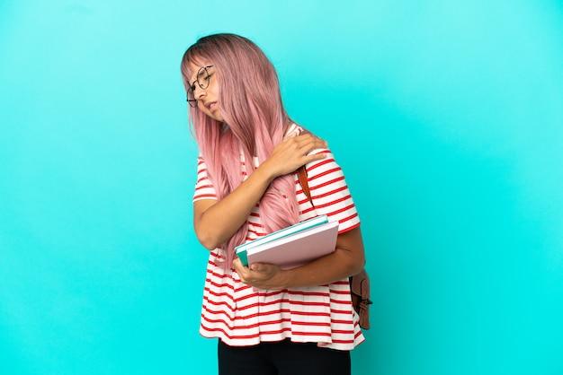 Молодая студентка с розовыми волосами, изолированными на синем фоне, страдает от боли в плече за то, что приложила усилия