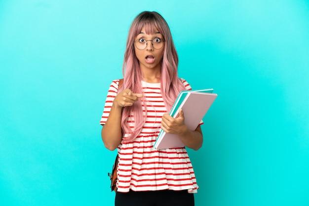 Молодая студентка с розовыми волосами, изолированными на синем фоне, удивлена и указывает вперед