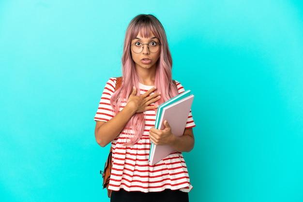 Молодая студентка с розовыми волосами на синем фоне удивлена и шокирована, глядя вправо
