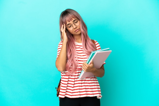 두통으로 파란색 배경에 고립 된 분홍색 머리를 가진 젊은 학생 여자